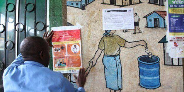 7월 31일 라이베리아의 몬로비아에서 한 간호사가 에볼라 바이러스에 대한 정보를 담은 종이를 공공의료센터에 게시하고