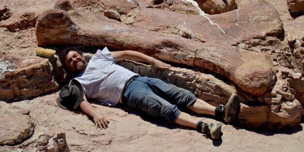 공룡화석 발굴에 참여한 한 연구자가 역사상 최대 크기의 공룡 뼈 옆에 누워 사진을