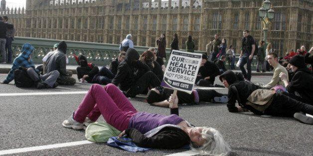 2011년 10월9일 영국 런던 중심의 웨스트민스터 다리에서 보수당 연립정권의 국가보건서비스(NHS) 민영화 움직임에 반대하는 시민들이 시위를 벌이고 있다. 친시장적인 연립정권은 복지급여를...