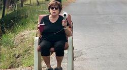 한 할머니가 도로에서 헤어드라이어를 들고 있는