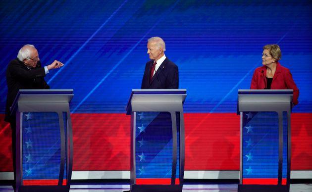 Former Vice President Joe Biden, center, and Sen. Elizabeth Warren, D-Mass., right, listen as Sen. Bernie...
