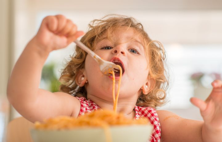 Beautiful blond child eating spaghetti with fork at home