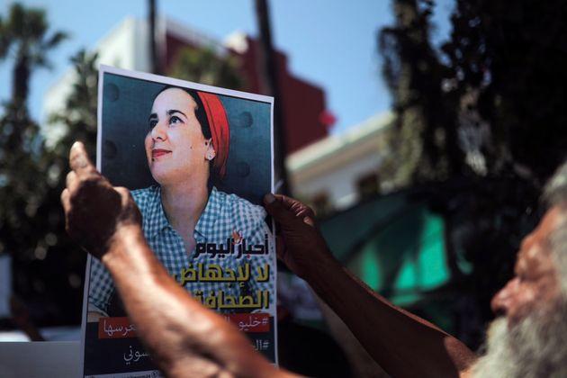 Un hombre sostiene una pancarta durante una manifestación afuera de una corte como solidaridad hacia...