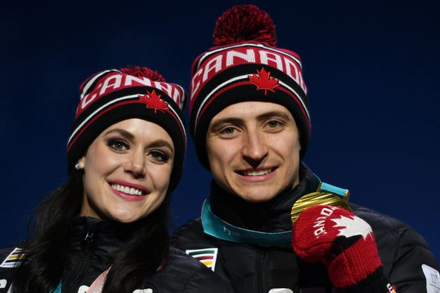 Canadian Olympic gold medallists Tessa Virtue and Scott Moir pose on the podium during a medal ceremony...
