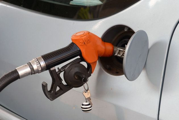 An employee refuels a vehicle with fuel at a petrol station on September 16, 2013 in Rabat. Fuel prices...