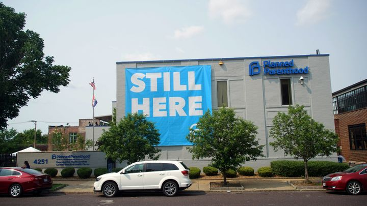 """A banner stating """"STILL HERE"""" hangs on the side of the Planned Parenthood Building after a judge granted a temporary restrain"""