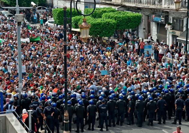 TOPSHOT - Algerian security forces form a human barrier in front of demonstrators taking part in a rally...