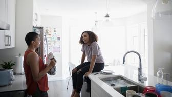 Mother and teenage daughter doing dishes, talking in kitchen