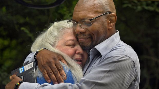 CHARLOTTESVILLE, VA JUL 07: - (L) Historic researcher Jane Smith gets a hug of thanks from Don Gathers just after the ceremony that acknowledged a brutal lynching 120 years ago. It was Smith who learned of the hanging from an old newspaper and successfully set out to fund the actual site of the crime. -120 years ago a black Charlottesville man, John Henry James, was lynched by a mob near the railroad tracks not far from downtown, Charlottesville, Virginia. Today the site of the lynching was recognized and dirt from the crime area was collected. Some of the soil will be taken to the Lynching Museum and Memorial in Montgomery, Alabama. (Photo by Michael S. Williamson/The Washington Post via Getty Images)