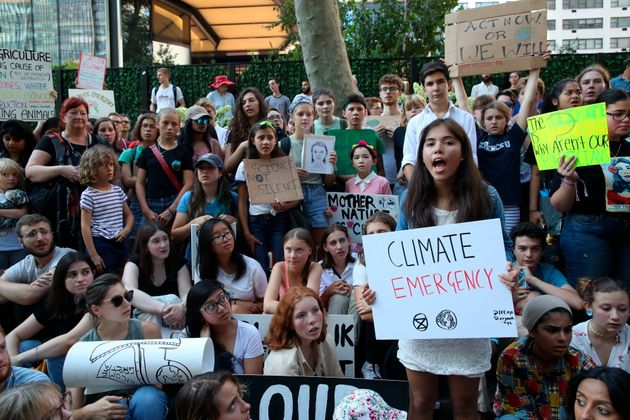 Swedish environmental activist Greta Thunberg, center in orange shirt, participates in a Climate Strike...