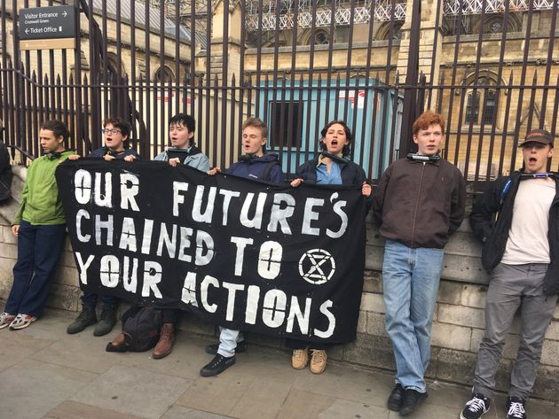 Protesters from the youth wing of Extinction Rebellion tie themselves to a fence outside