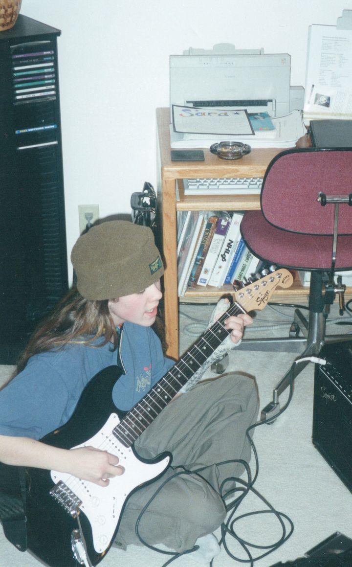 Sara playing electric guitar.
