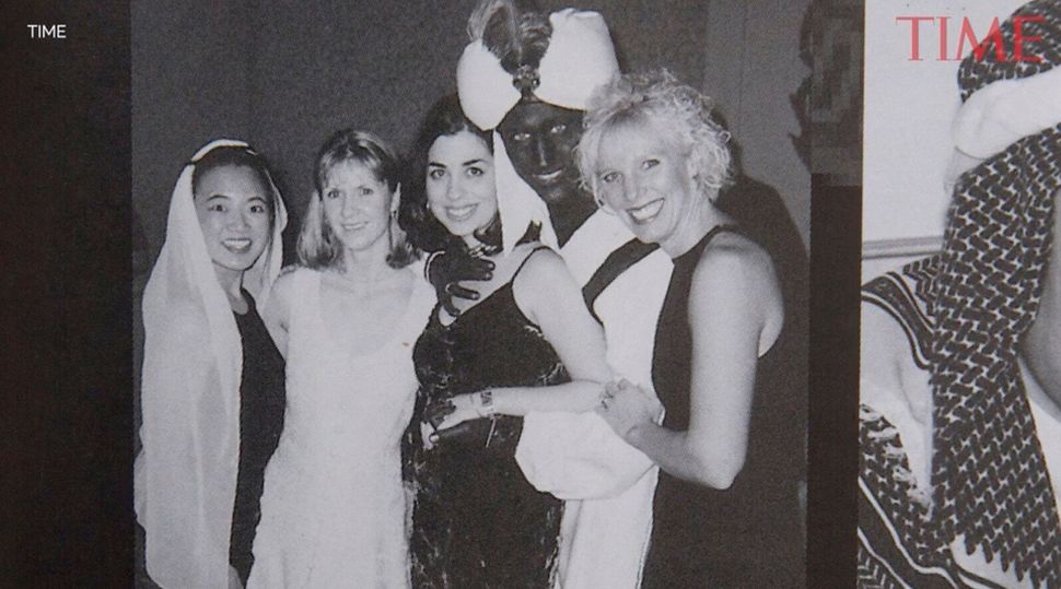 A yearbook photo shows Justin Trudeau, second from right, at a 2001 costume party with his hands and...