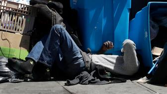 """FILE -  In this Aug. 21, 2019, file photo, a homeless man sleeps in front of recycling bins and garbage on a street corner in San Francisco. California Gov. Gavin Newsom is asking President Trump to approve more housing vouchers as Trump's administration weighs in on the most populous state's massive homeless problem. The Democratic governor on Monday, Sept. 16 sent the Republican president a letter asserting that """"shelter solves sleep, but only housing solves homelessness."""" Officials did not immediately respond.  (AP Photo/Jeff Chiu, File)"""
