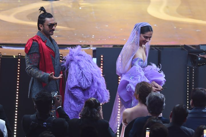Ranveer Singh carries the back Deepika Padukone's dress during IIFA Awards.
