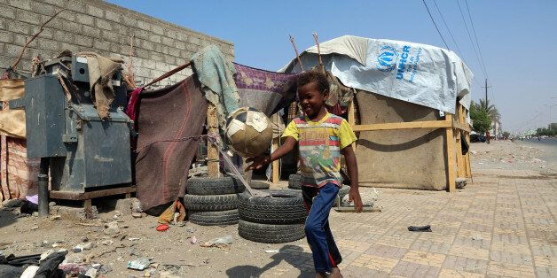 A displaced Yemeni child plays with a ball next to their makeshift shelter on a street in the Yemeni...