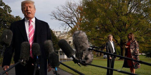 WASHINGTON, DC - NOVEMBER 21: U.S. first lady Melania Trump (R) and her son Barron Trump listen to President...