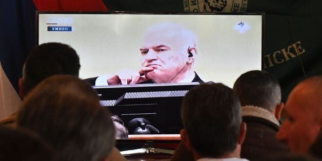 Former Bosnian Serbian commander Ratko Mladic appears on a TV screen wher people gather to watch a live...