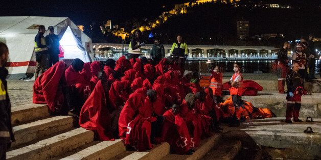 A group of migrants just being rescued in the Mediterranean sea, arrives at the harbour of Malaga, where...