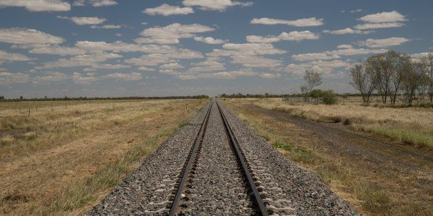 A railway line in the Queensland outback with a blue sky with