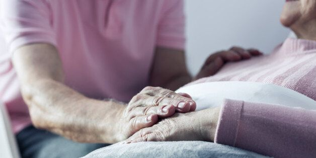 Senior man holding hand of his ill wife, close