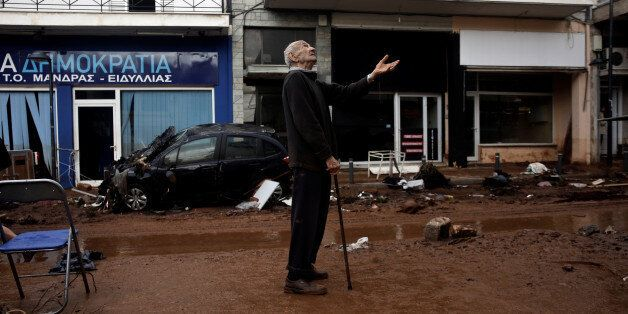A local gestures as he stands next to a muddy street, following flash floods which hit areas west of...