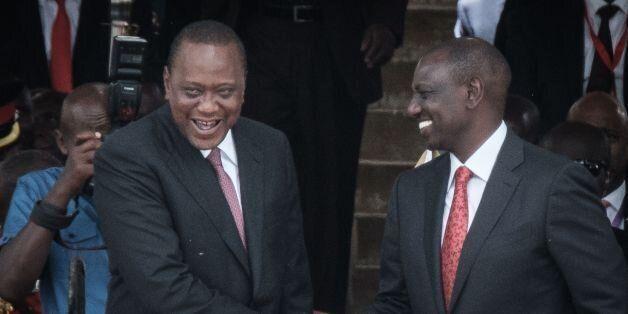 Kenya's President Uhuru Kenyatta (L) and Vice-President William Ruto shake hands after taking oath of...