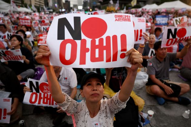 SEOUL, SOUTH KOREA - AUGUST 15: South Koreans hold up signs denouncing Japanese Prime Minister Shinzo...