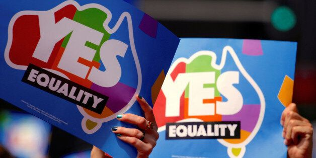 People participating in a march hold aloft posters supporting a 'Yes' vote in a non-binding poll, conducted...