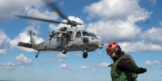 A helicopter landing signal crew member gestures as a helicopter takes off from the deck of the USS George...