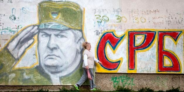 A wiman walks past a graffiti depicting former Bosnian Serb commander Ratko Mladic and reading 'Serbia'...