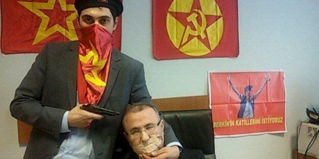 A gunman poses with Prosecutor Mehmet Selim Kiraz with a gun on his head after being taken hostage in...