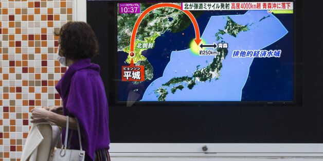 A pedestrian walks past a screen broadcasting a map of Japan and the Korean Peninsula during a news program...