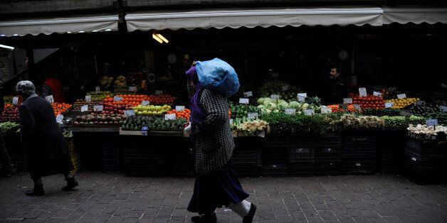 A woman walks past a vegetable market in central Athens, Greece February 11, 2017. REUTERS/Michalis