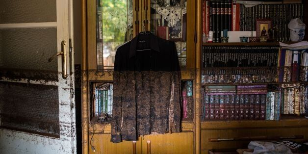 A photo shows a shirt hanging near a bookcase marked with mud from floodwater in a house in Mandra, northwest...