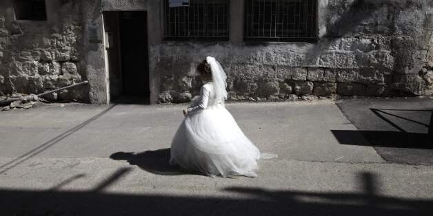 TOPSHOT - An ultra-Orthodox Jewish girl wearing a bride outfit walks in the street during a school Purim...