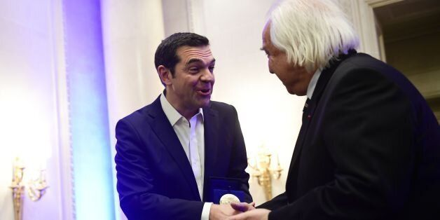 Greek Prime Minister Alexis Tsipras (L) shakes hands with International Politics magazine director Patrick...