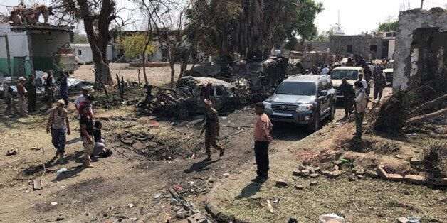 Yemeni men and security forces inspect the damage in the aftermath of an attack claimed by the Islamic...