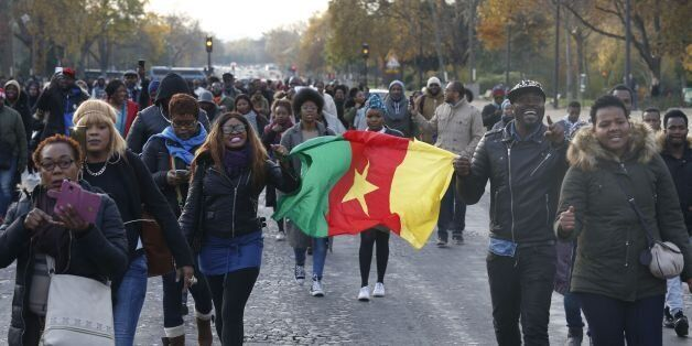 Woman hold a flag of Cameroon during a march against 'slavery in Libya' on November 18, 2017 in Paris....