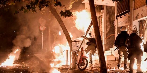 A petrol bomb explodes next to anti-riot policemen in downtown Athens on November 17, 2017, during clashes...