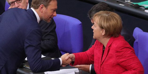 Christian Lindner, leader of the Free Democratic Party (FDP), left, shakes hands with Angela Merkel,...