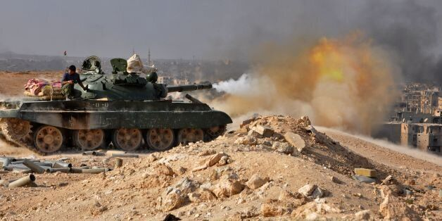 A Syrian government forces' tank fires rounds in the eastern city of Deir Ezzor during an operation against...