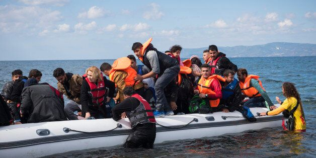 Lesbos, Greece- October 25, 2015: A volunteer lifeguard assists migrants out of their boat after they...