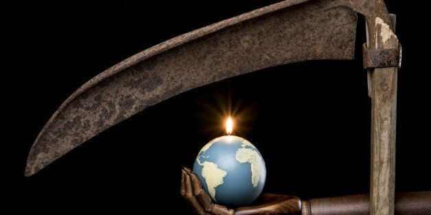 Black hand holding a bomb in the shape of Earth with the light on. Isolated on black background. With...