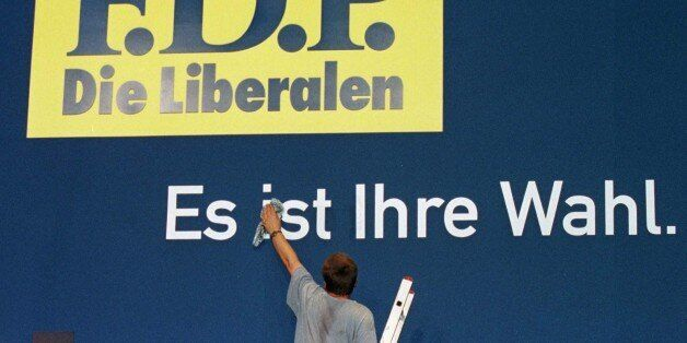 A worker gives a final touch to a poster for Germany's Free Democrats (FDP) with the