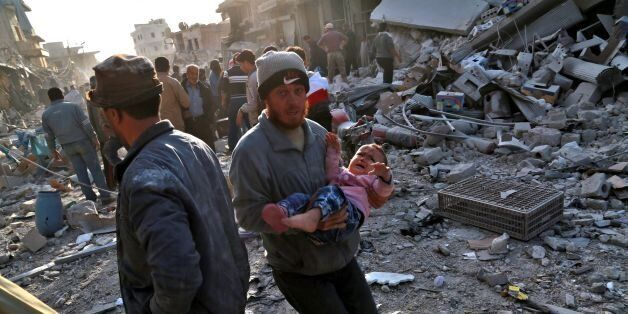 A Syrian man carries a child following a reported airstrike on the rebel-held town of Atareb in Syria's...