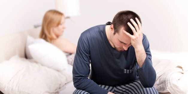 Upset man sitting on the bed with woman on the back