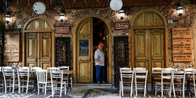 A man exits a tavern as empty tables stand outside in the Psyri neighborhood of Athens, Greece, on Friday,...