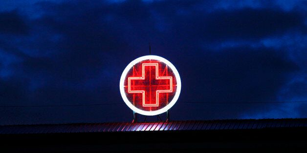 A red neon cross is seen on the rooftop of the Evangelismos State General Hospital in Athens May 30,...