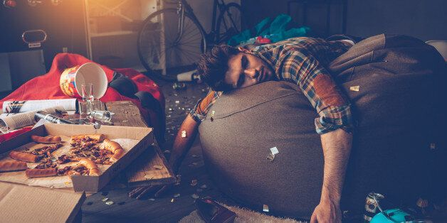 Young handsome man passed out on bean bag with joystick in his hand in messy room after